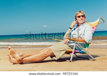 Business man calling by cell phone on the beach in Hawaii