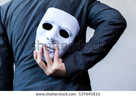 Business man carrying white mask to his body indicating Business fraud and faking business partnership