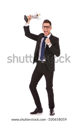 Business man celebrating with trophy on white background