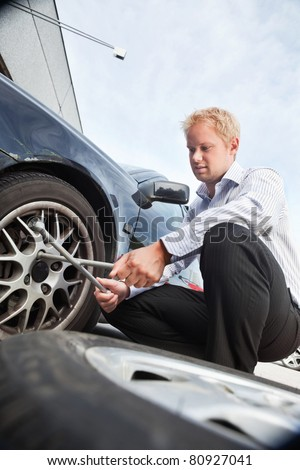 Business man changing a tire on the street