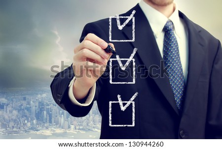 Business man checking off check boxes with cityscape background