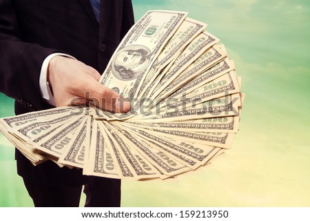 Business Man Displaying a Spread of Cash over Vintage Sky Background