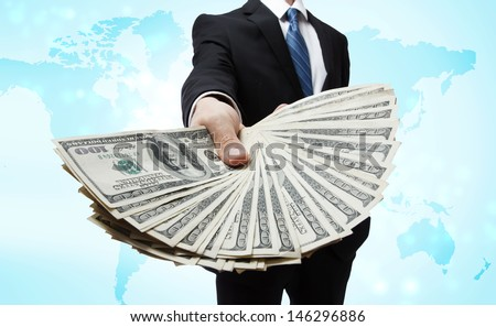 Business Man Displaying Spread of Cash over World Map