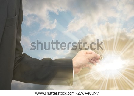Business man donate dollar coin over bright overcast sky with sun star leak out of cloud