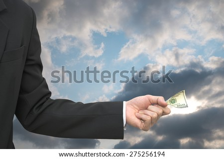 Business man donate 100 dollar note over bright overcast sky with sun light leak out of cloud