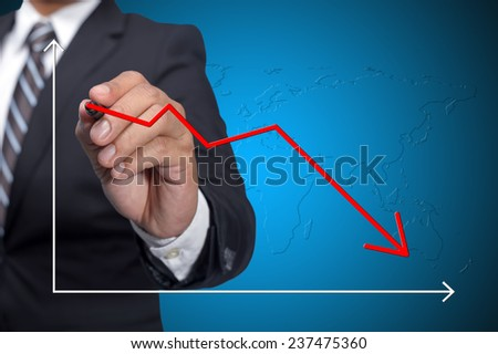 Business man drawing decline graph over blue background