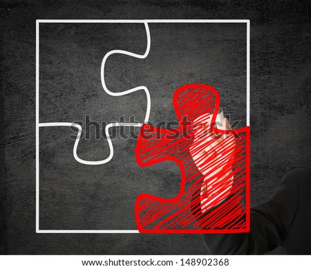 Business man drawing missing jigsaw puzzle piece on transparent drawing board - solution or teamwork concept