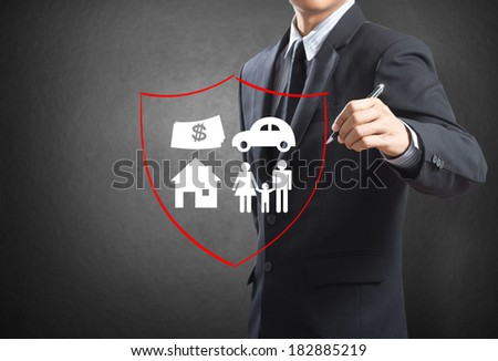 Business man drawing shield protecting family, house, car money.  insurance concept