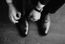 Business man dressing up with classic, elegant shoes. Groom wearing shoes on wedding day, tying the laces and preparing. Black and white photo