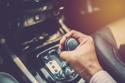 Business man driver hand shifting the gear stick. Vintage filter