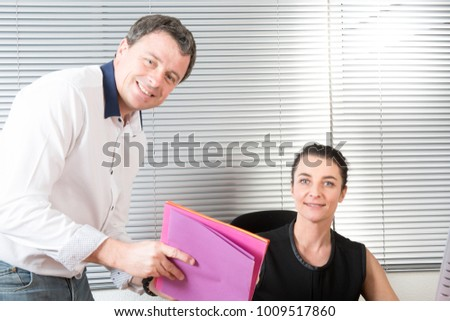 Business man explaining something to a woman in an office #1009517860