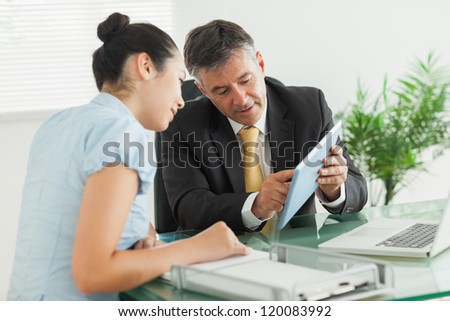 Business man explaining something to a woman with a digital tablet in an office