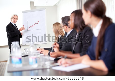 Business man explaining to his sales team about achieving preset targets