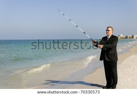 Business man fishing at the ocean with hotels in the background.