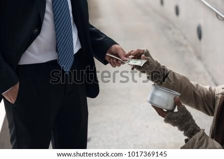 Business man giving one dollar bill money to beggar o homeless guy at city walk in urban town. Poverty and social issue concept. Give and share with sympathy