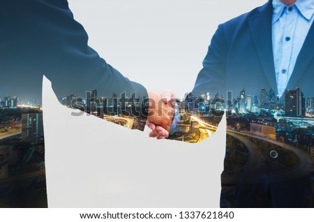 business man greeting with shaking hands partnership successful corporate dealing working together concept with double exposure of night cityscape in city metropolis landscape. #1337621840