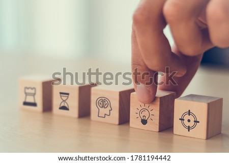 business man hand arranging wood block . icon of business strategy including element with goal, idea, leadership, management of time, Knowledge, Initiative, Human relations with copy space