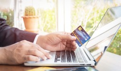 Business man hand hold credit card to shopping internet online bill on computer, Debit saving purchase buy on table background. Shopaholic people retail pay sale money, bank terminal account concept