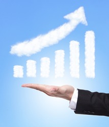 Business man hand holding a growth graph ( made by cloud ) in the air with blue sky, finance and business concept