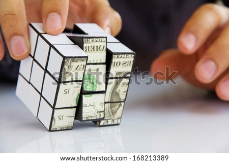 business man hand holding a rubik's cube,money concept