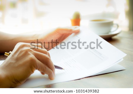 Business man hand holding pen over agreement form