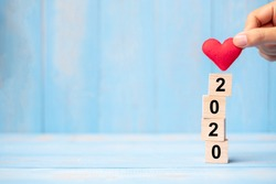 Business man hand holding red heart shape over 2020 wooden cubes on blue table background with copy space for text. Business, Resolution, New Year New You and Happy Valentine's day holiday concept