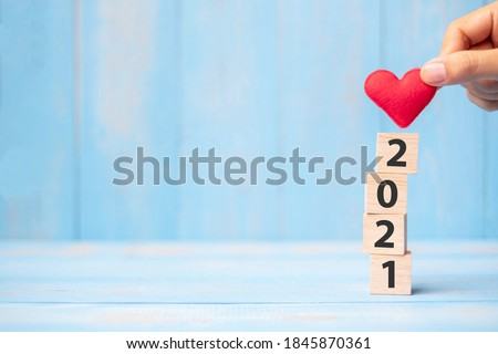 Business man hand holding red heart shape over 2021 wooden cubes on blue table background with copy space for text. Business, Resolution, New Year New You and Happy Valentine's day holiday concept