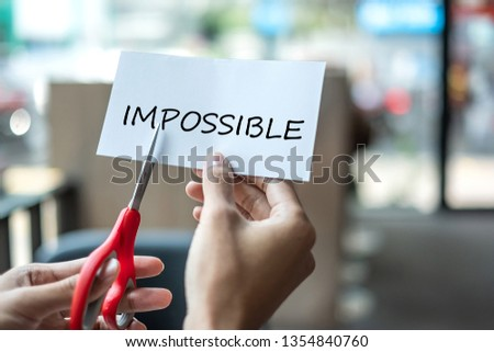 Business man hand holding red scissors and cutting white paper with the text IMPOSSIBLE, change word to POSSIBLE. challenge, positive thinking and success concept #1354840760