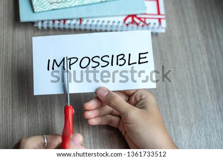 Business man hand holding red scissors and cutting white paper with the text IMPOSSIBLE, change word to POSSIBLE. challenge, positive thinking and success concept #1361733512