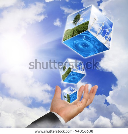 Business man hand holding with nature water drop and wind  turbines farm on sky