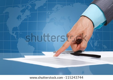 business man hand in elegant suit point finger at the document, paper on the desk over digital globe map background, sign up contract Concept of global international business collaboration