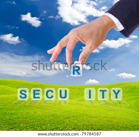 business man hand made security word buttons on green grass meadow
