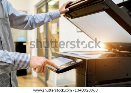 Business man Hand press button on panel of printer, printer scanner laser office copy machine supplies start