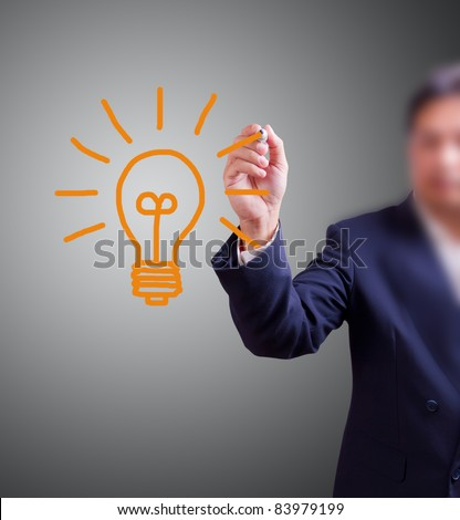 business man Hand with pen drawing light bulb