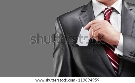 Business man handing a blank business card isolated on gray background High resolution