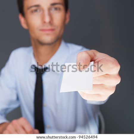 Business man handing a blank business card over grey background