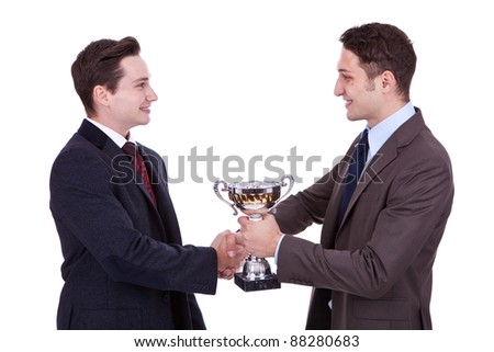 business man handing a trophy to his winning coleague and handshake him