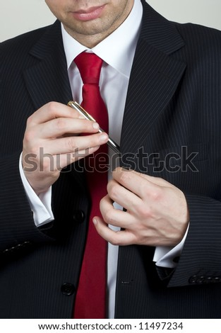 Business man handing out a pen to sign a contract