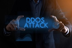 Business man hands holding inscription DDOS ATTACK with different graphs on the background.automation technology concept.