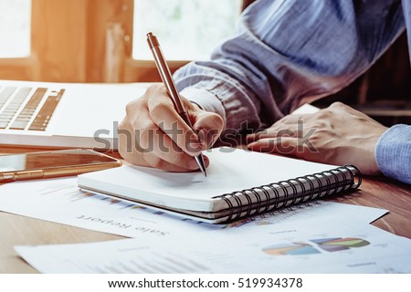 Business man hands with pen writing notebook  on office desk table close up. Business concept.