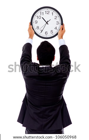 Business man hanging a clock on the wall