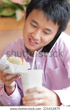 business man having lunch and eat fast food in a restaurant, asian
