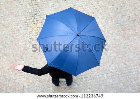 Business man hidden under umbrella and checking if it\'s raining