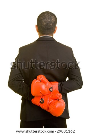 Business man hiding boxing gloves behind his back