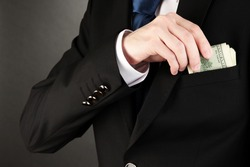 Business man hiding money in pocket on black background