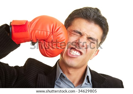 Business man hitting himself with a red boxing glove in the face