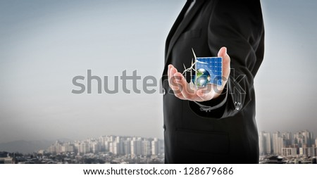 Business man hold Alternative Energy (solar cell, earth, wind turbine ) Elements of this image furnished by NASA - stock photo