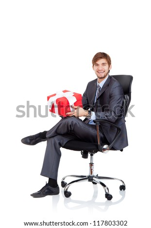 Business man hold gift box in chair, businessman give red present, sitting in armchair, happy smile, Isolated over white background