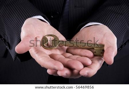 Business man holding a a golden key