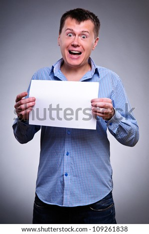 Business man holding a blank banner and looking down to copy space. portrait on gray background